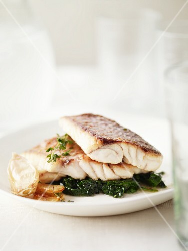 Fish fillet on a bed of spinach with garlic