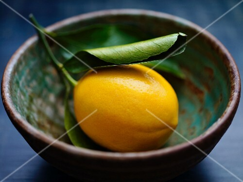 A lemon with a leaf in a ceramic bowl