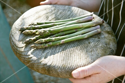 Green asparagus spears on a wooden platter