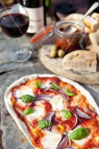 A stone oven pizza with focaccia, antipasti and wine in the background
