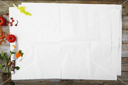 An arrangement of vegetables on the edge of apiece of paper