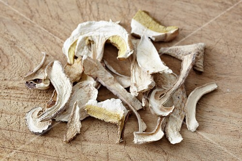 Dried sliced porcini mushrooms on a wooden board