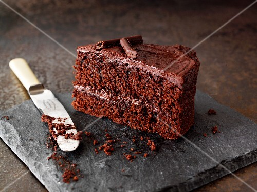 A slice of chocolate cake on a stone platter with a knife