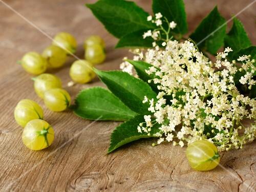 Elderflowers and gooseberries on a wooden table