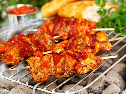 Pork skewers with salsa and bread on a barbecue