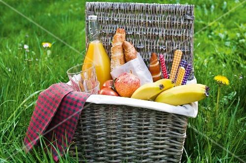 A picnic basket filled with fruit, rolls and orange juice