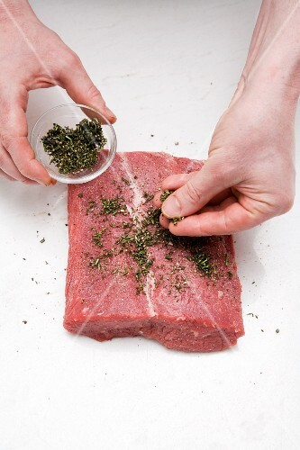 Herbs being strewn onto a slice of raw beef
