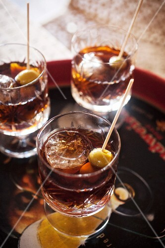 Vermouth with ice cubes and olive skewers