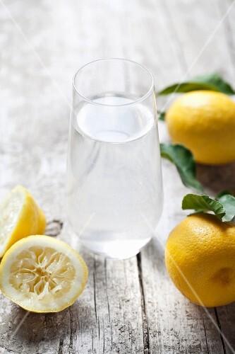 A glass of lemon water and fresh lemons