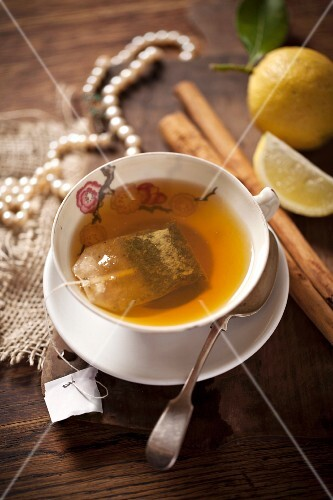 A cup of tea with a tea bag, cinnamon stick and lemons