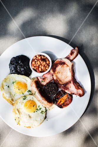 An English breakfast with fried eggs, sausage, bacon, black pudding, baked beans and fried tomatoes