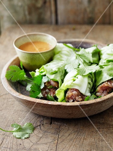 Lettuce wraps filled with raw minced pork with herbs and served with a dip