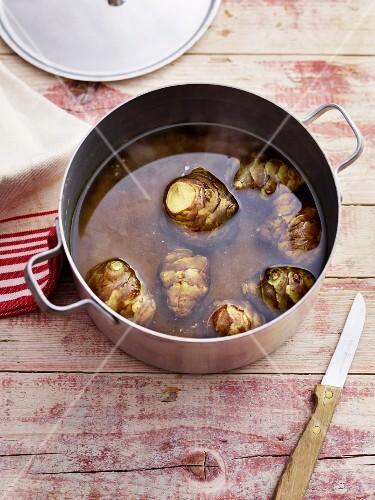 Unpeeled Jerusalem artichokes in a pot of water