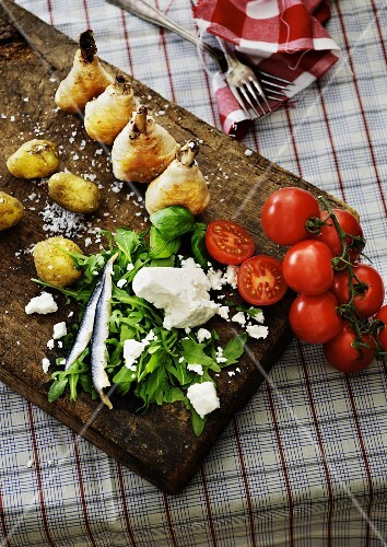 Roast chicken legs, potatoes, rocket, tomatoes and sheep's cheese on a wooden board