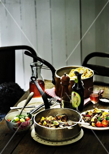 A Mediterranean dish with beef and vegetables served with pasta and a cucumber and tomato salad