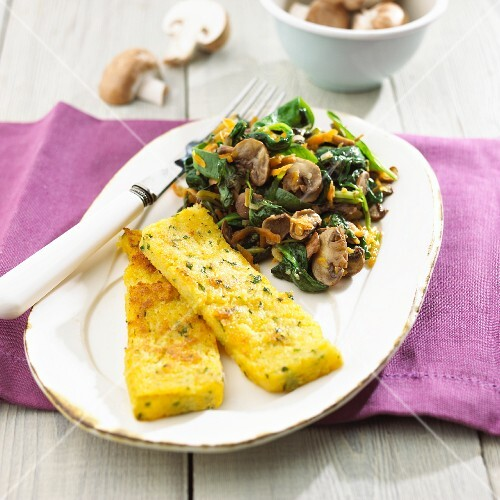 Polenta slices with spinach and mushrooms
