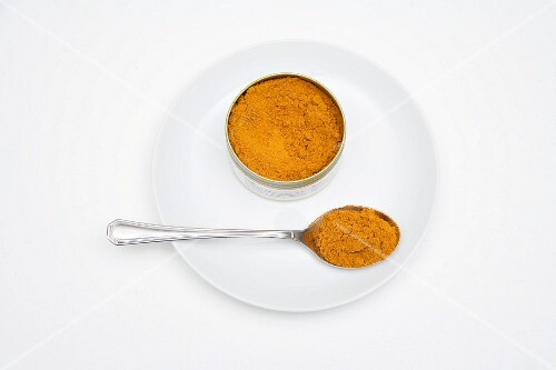 Madras curry powder in a tin and on a spoon