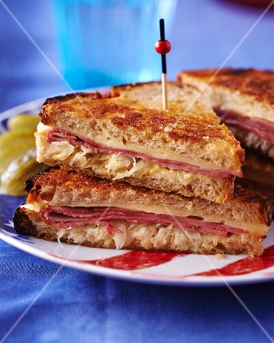 A toasted sandwich with pastrami, cheese and sauerkraut