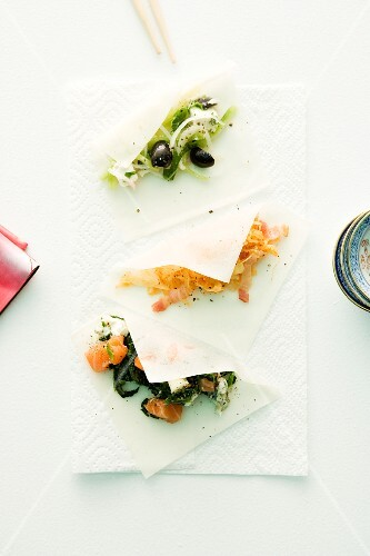 Three sheets of rice paper with various savoury fillings for spring rolls