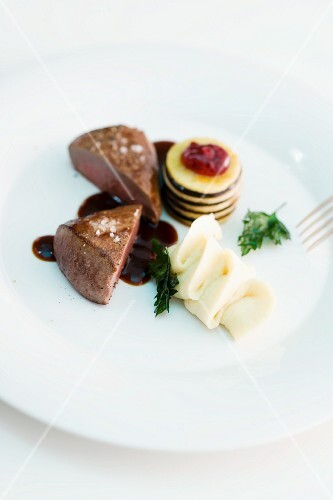 Saddle of venison with a dark sauce, mashed potatoes and an apple and cranberry tower