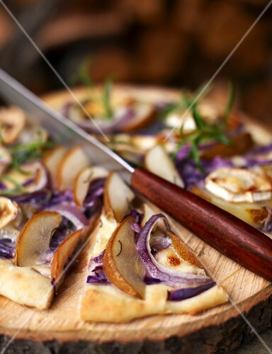 An autumnal pizza with pears, goat's cheese and red onions, sliced