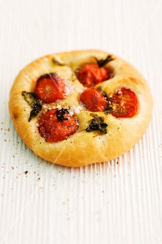Focaccia with cherry tomatoes and basil on a wooden surface