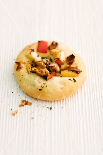 Focaccia with apple, walnuts and marjoram on a wooden surface