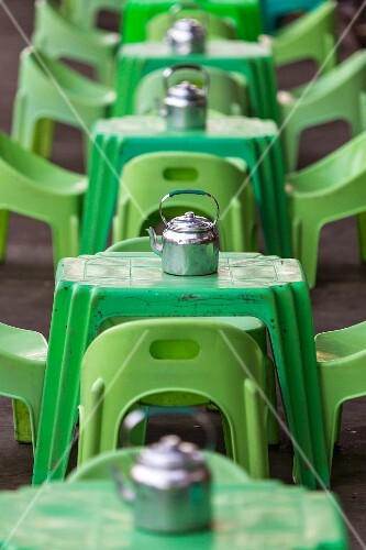 Green plastic tables and stools with shiny teapots