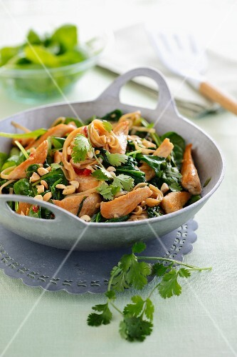 Fried spinach with chicken breast, peanuts and coriander