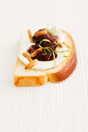 A slice of brioche topped with strawberry jam, pine nuts and basil