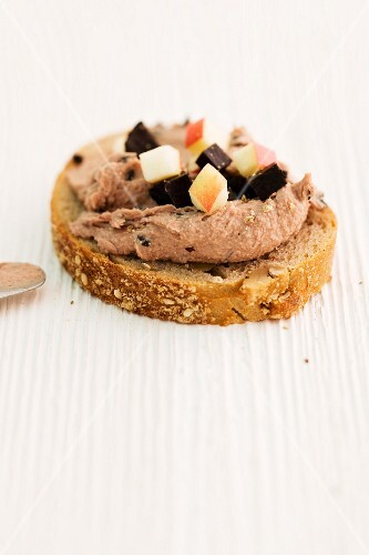 A slice of bread topped with truffled goose liver and diced apple