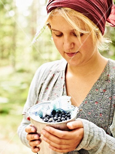 A girl holding a small bucket of freshly picked blueberries