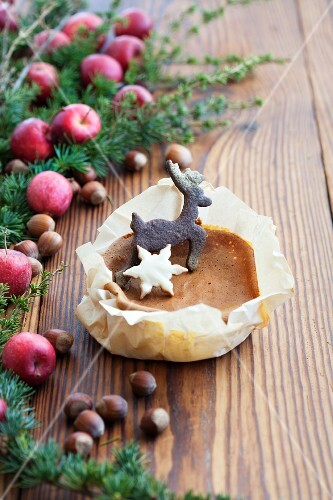 A Christmas biscuit on a mini sponge cake on a wooden surface