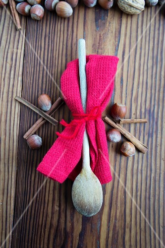 A wooden spoon and a tea towel between hazelnuts and cinnamon sticks
