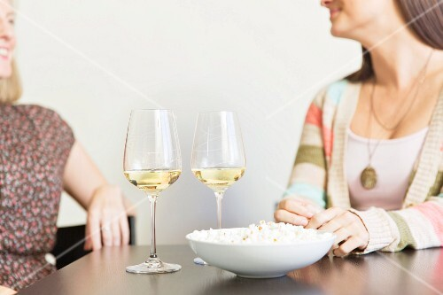 Two women sitting at a table with a bowl of popcorn and glasses of wine