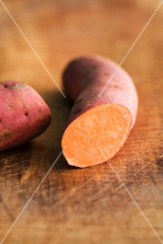 A red sweet potato, sliced, on a wooden board