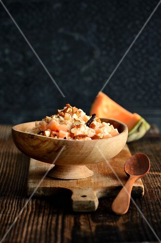 Rice pudding with melon and almonds in a wooden bowl
