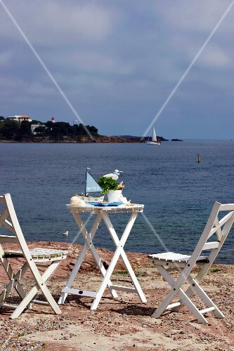 A table and chairs made from white painted wood on the beach