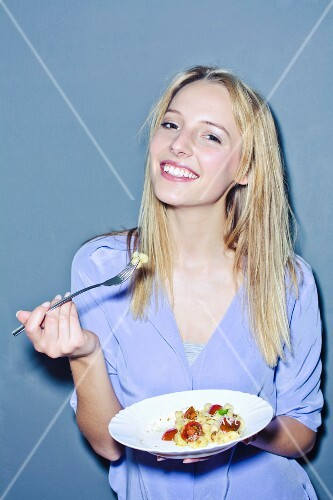 A smiling woman eating