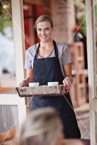 A waitress with a tray and cups of coffee