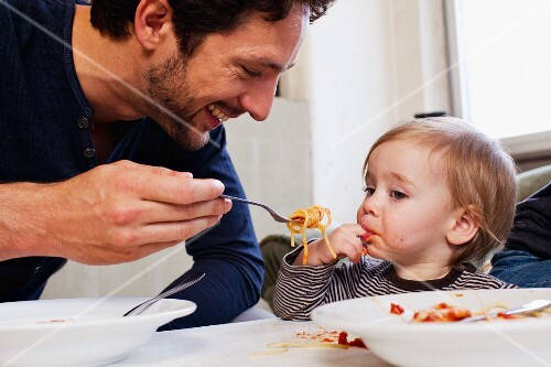 A father feeding his little daughter