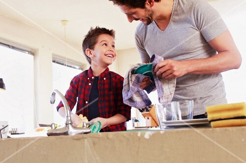 A father and son working happily together in the kitchen