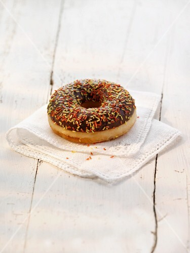 A doughnut with chocolate glaze and colourful sugar sprinkles