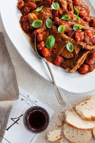 Lamb chops with cherry tomatoes and basil served with baguette and red wine