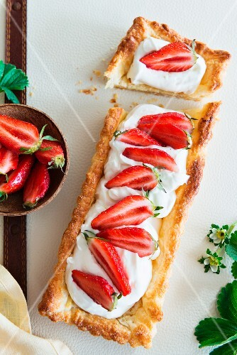 A puff pastry tart topped with yoghurt and strawberries, sliced
