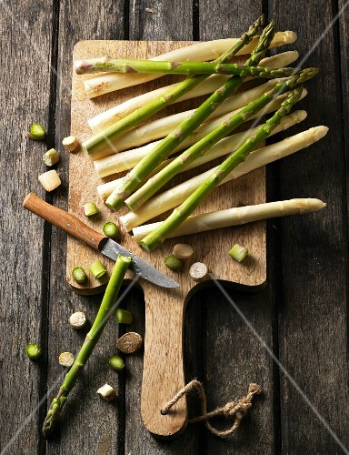 White and green asparagus with the ends cut off on a chopping board