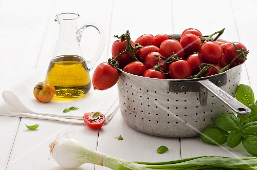 Tomatoes in a colander next to basil, onions and olive oil