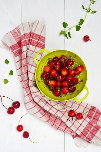 Fresh cherries in a green colander
