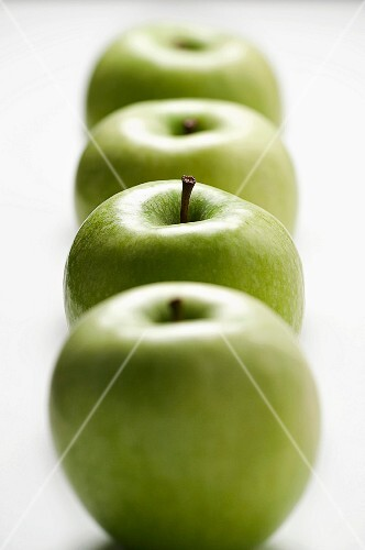 A row of four green apples