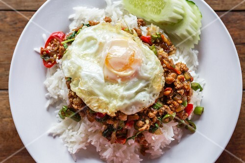 Pork with chilli and Thai basil on a bed of rice top with a fried egg